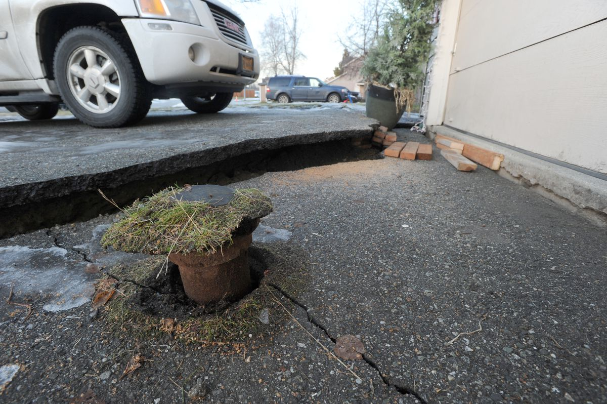 A corner of Nikki and Mike Rose's home dropped during the Nov. 30 earthquake, causing the driveway pavement to crack. The water shutoff, or keybox, remained at its original height. Photographed Dec. 3, 2018. (Anne Raup / ADN)