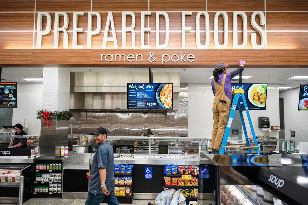 Carla Green touches up a sign in the Midtown Mall Carrs store on Tuesday. (Loren Holmes / ADN)
