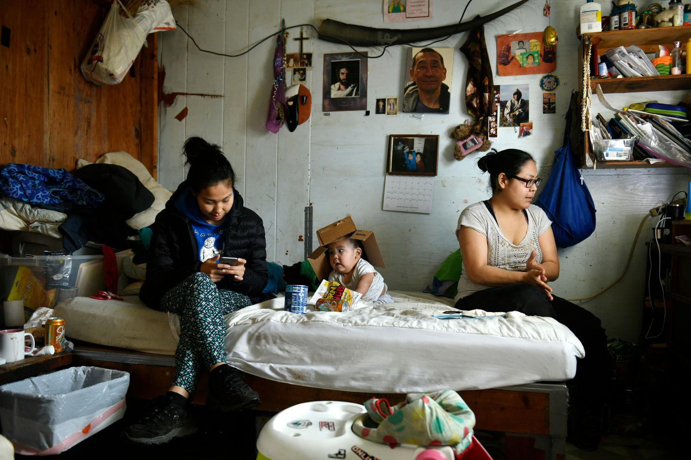 From left, Hannah John, 7-month-old Tom John, and Jocelyn spend time in their Newtok home. The family expected to move to Mertarvik within weeks. (Marc Lester / ADN)
