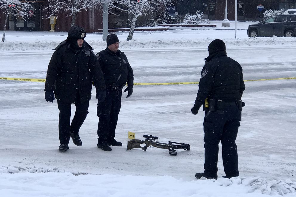 APD officers stand near a cross bow lying on Huffman Road near intersection of Industry Way in South Anchorage as they secure the scene of an officer-involved shooting on Sunday, Jan. 12, 2020. (Bill Roth / ADN)