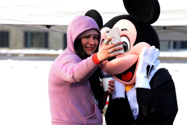 A runner takes a selfie with Mickey Mouse before the start of the race. (Photo by Bob Hallinen)