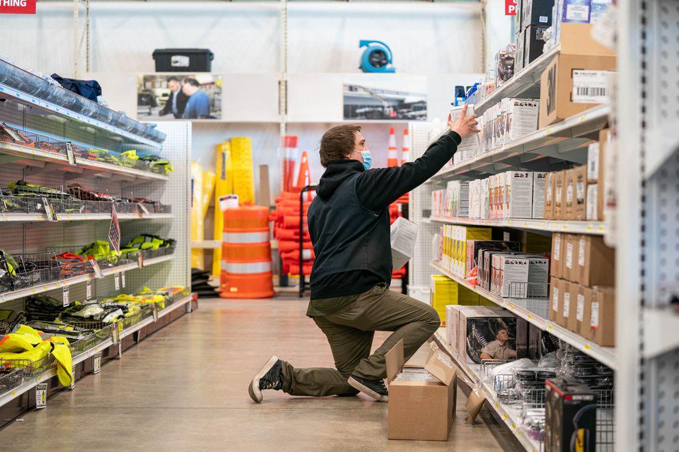 Salesperson Trent Simonson stocks shelves at Alaska Industrial Hardware on Friday, April 9, 2021. (Loren Holmes / ADN)