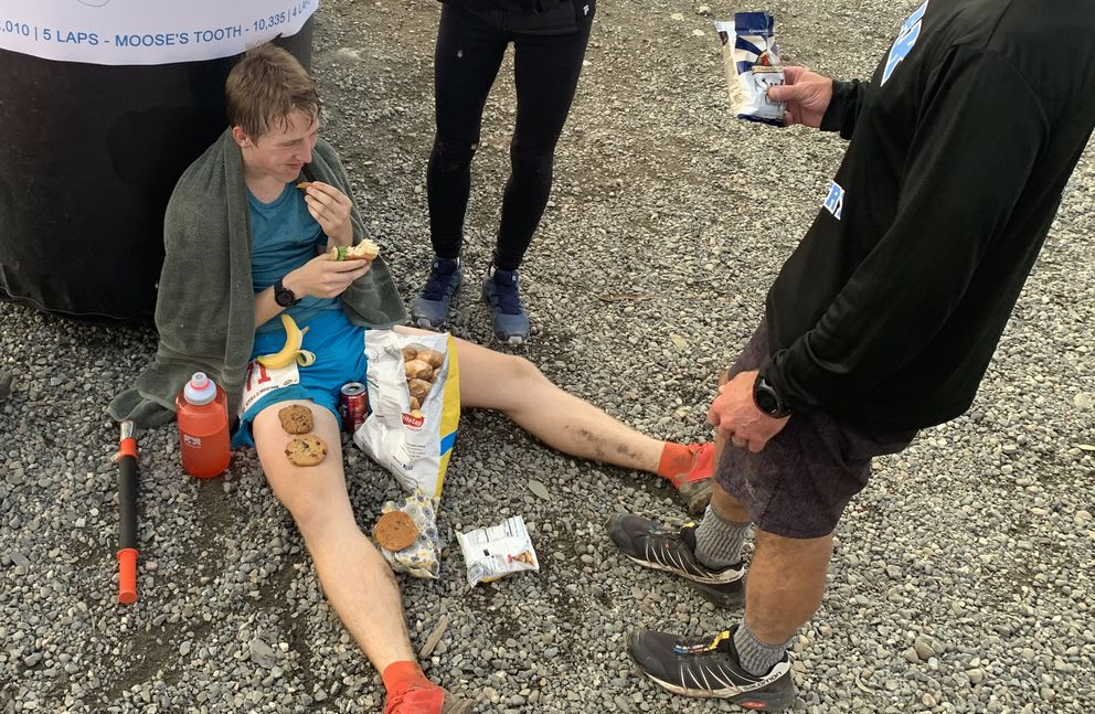 Mikey Connelly eats a sandwich, cookies, a banana, potato chips and soda after winning the Alyeska Climbathon on Saturday, Sept. 14, 2019 at Mount Alyeska in Girdwood. (Matt Tunseth / Chugiak-Eagle River Star)