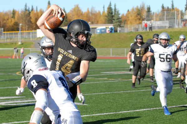 South quarterback Spencer Martin tries to break a tackle during the Wolverines' 50-7 nonconference football win over Eagle River on Saturday, Sept. 29, 2018 at South High. (Matt Tunseth/Chugiak-Eagle River Star)