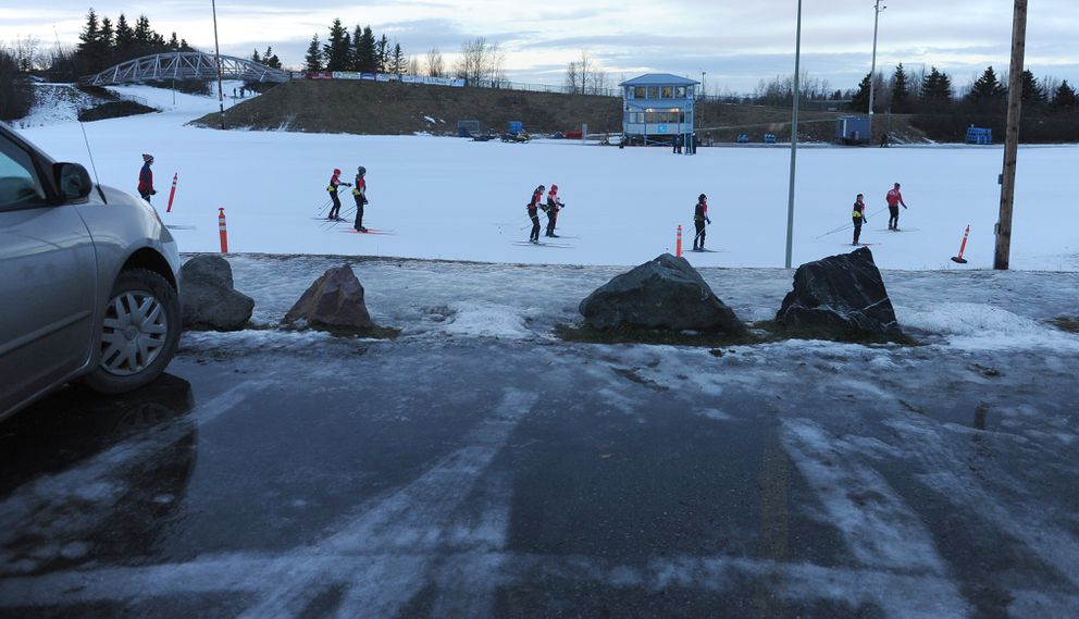 Youth skiers with the Alaska Winter Stars club team train Tuesday at Kincaid Park, as water pools atop ice in the parking lot. (Bob Hallinen / ADN)