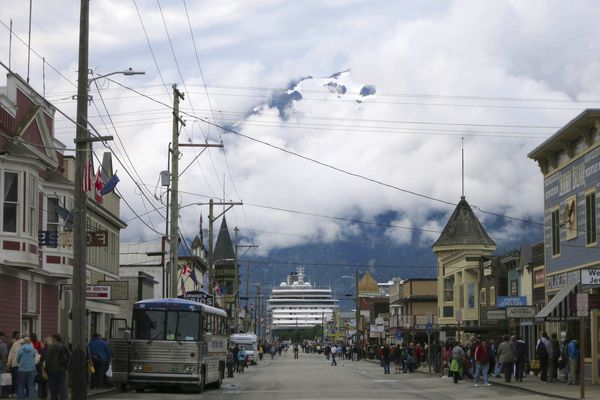 FILE - This July 29, 2014, file photo, shows a cruise ship docked in Skagway, Alaska, as passengers tour the town. The Alaska port city, nearly entirely dependent upon cruise ship tourism, wants to share its federal coronavirus relief funds with workers in town. The city of Skagway posted an application on its website inviting residents to apply for up to $1,000 in relief funds to help with bills. Nearly half of Alaska's 2.2 million tourists arrive on cruise ships, but most companies have canceled their summer seasons, leaving workers here without much relief. (AP Photo/Kathy Matheson, File)