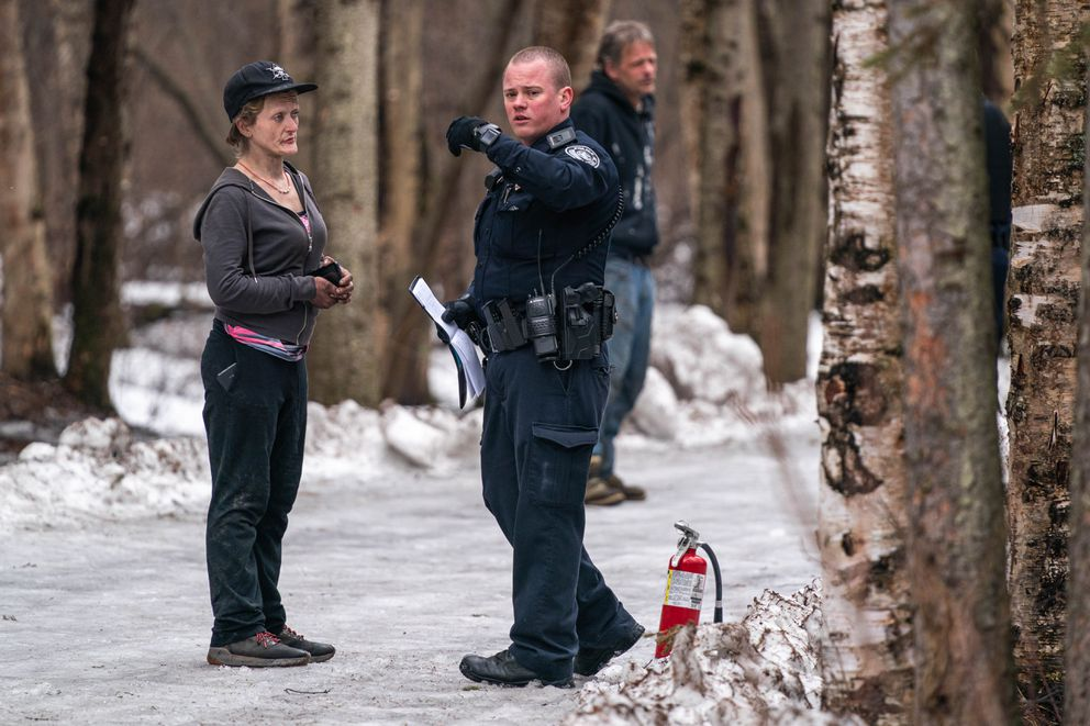 An Anchorage police officer interviews a witness to a fire at a homeless camp in the Chester Creek Greenbelt on Friday, April 17, 2020. (Loren Holmes / ADN)