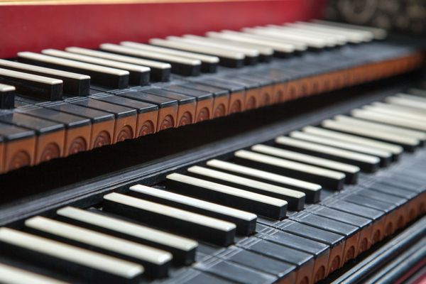 Old antique, historic, two rowed piano keyboard and beautiful ornaments on its forehead.