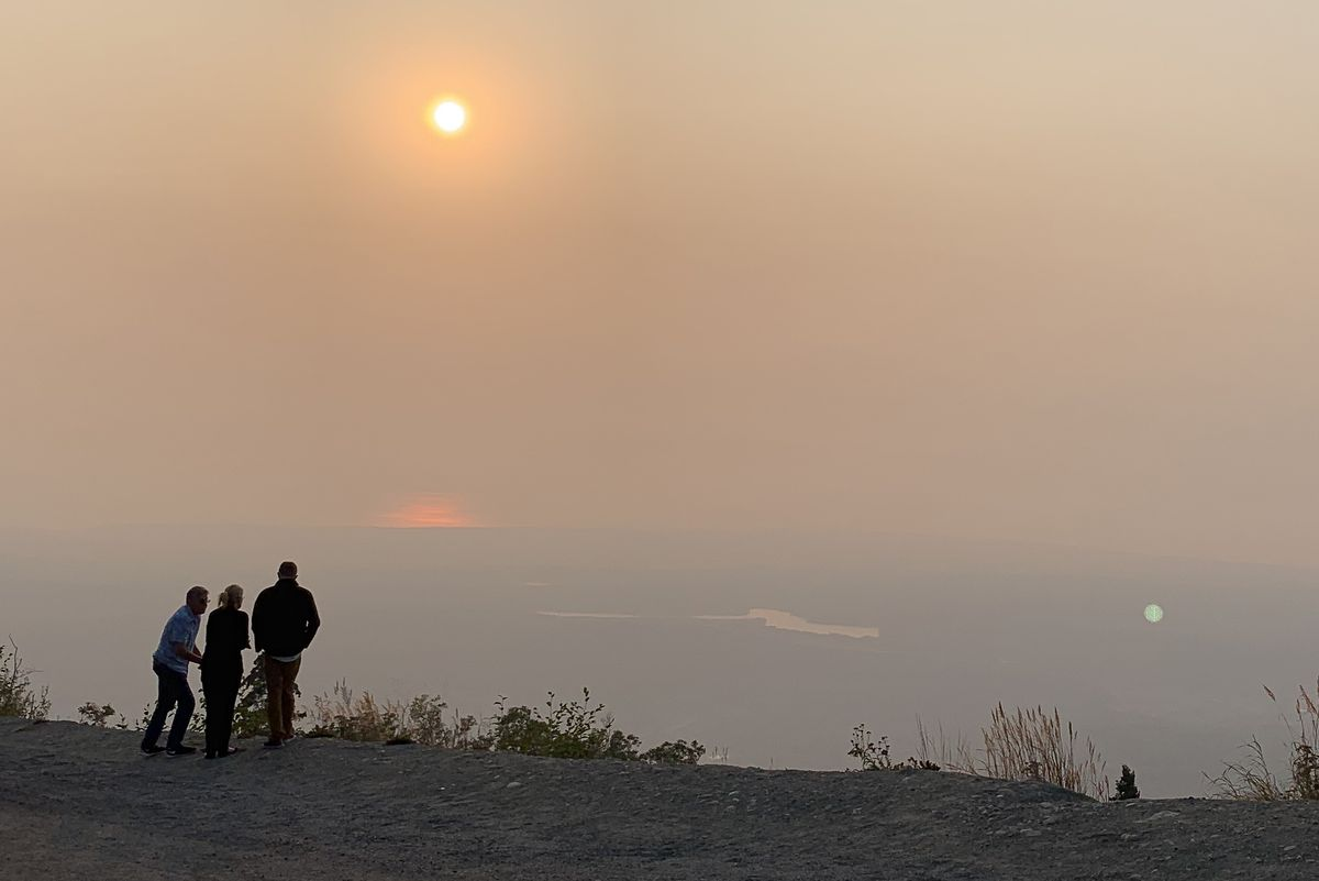 People watch the setting sun behind Knik Arm from a vantage point at the top of Skyline Drive in Eagle River as smoke from the Swan Lake wildfire drifts over the area on Tuesday, Aug. 20, 2019. (Matt Tunseth / ADN)