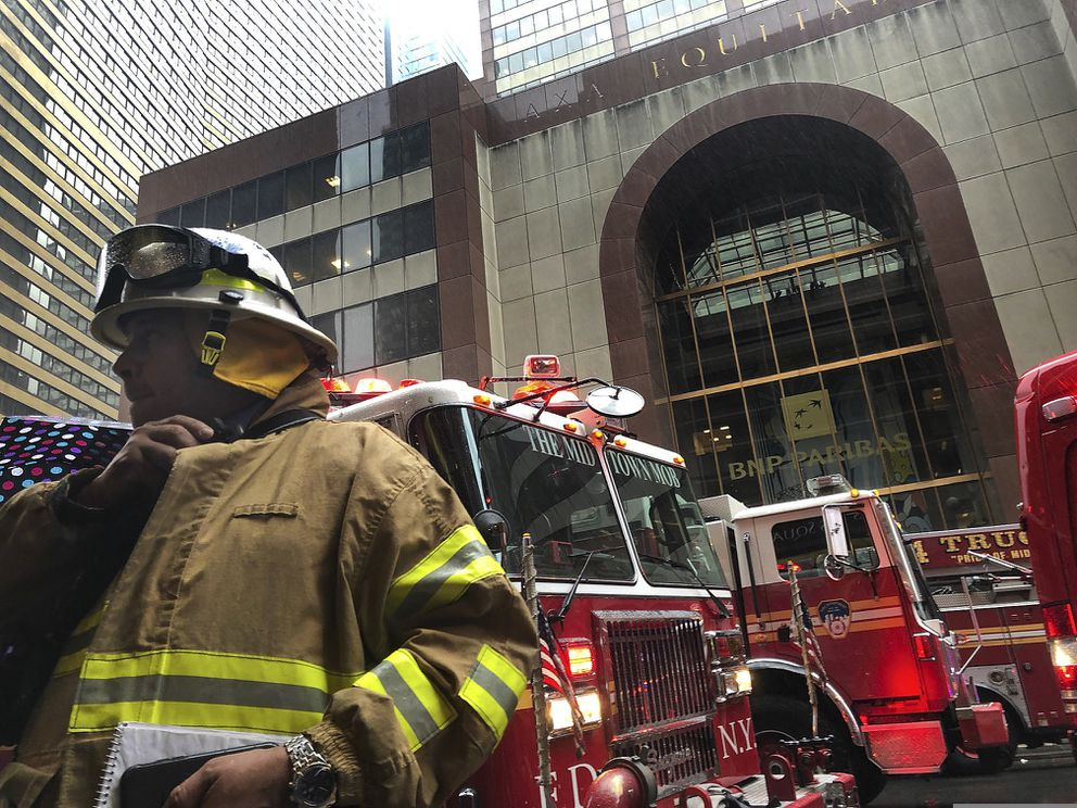 A New York City firefighter responds to the scene where a helicopter crash-landed on the roof of a midtown Manhattan skyscraper, Monday, June 10, 2019, in New York. (AP Photo/Mark Lennihan)