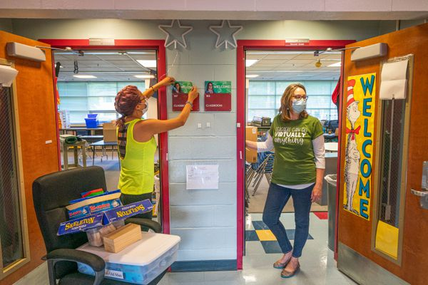 First-grade teacher Katrina Kim, left, takes her photo off of the door to her old classroom, preparing to move it to her new one on Thursday, Aug. 13, 2020 at Nunaka Valley Elementary School in Anchorage. At right is second-grade teacher Deborah Webb, wearing a shirt that says