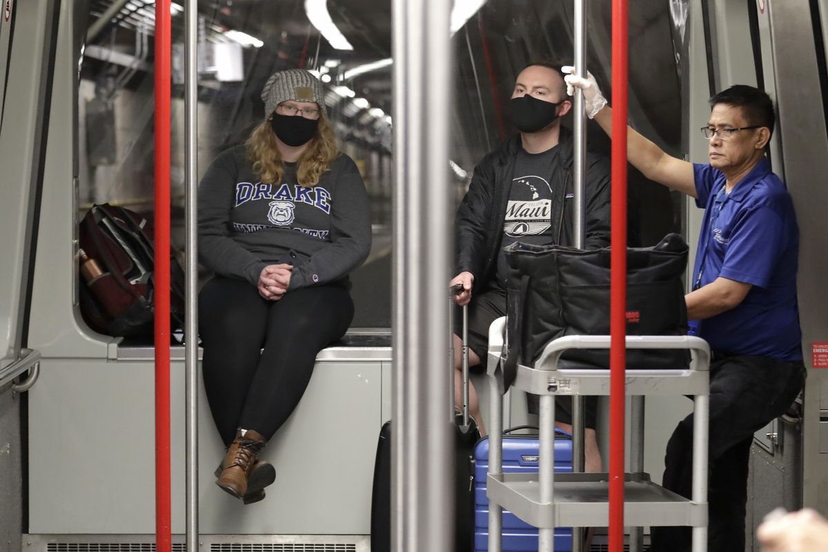 Travelers Meredith Ponder, left, and Coleby Hanisch, both of Des Moines, Iowa, wear masks to remind them not to touch their faces as they ride a train at Seattle-Tacoma International Airport Tuesday, March 3, 2020, in SeaTac, Wash. Health officials are encouraging the general public not to buy medical masks to ensure there are enough for health care workers. (AP Photo/Elaine Thompson)