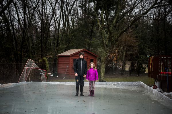 Jack Williams, 12, and his sister Cara, 8, in their family's melting ice rink in Waterloo, Ontario, Canada, Feb. 20, 2018. Homemade backyard rinks used to offer good skating in this part of Canada from early December into March; the tradition, deeply imbedded in Canada's national identity, is now dying off thanks to warmer temperatures. (Aaron Vincent Elkaim/The New York Times)