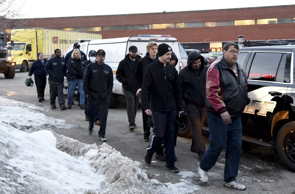 Employees are escorted from the scene of a shooting at a manufacturing plant Friday, Feb. 15, 2019, in Aurora, Ill., that police said left several people dead and several police officers wounded. (AP Photo/Matt Marton)