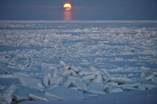 The moon is visible over sea ice from a road a few miles northeast of Utqiagvik (formerly Barrow) on Dec. 13, 2016. (Marc Lester / ADN)
