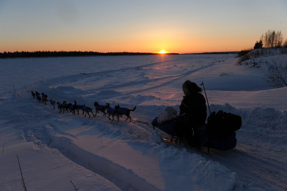 Iditarod musher Mark Selland drives his dog team onto the Yukon River at sunset as he leaves the village of Tanana during the 2017 Iditarod Trail Sled Dog Race on Wednesday, March 8, 2017. (Bob Hallinen / Alaska Dispatch News)