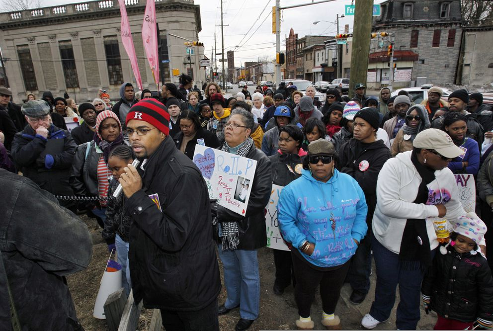 FILE - In this Feb. 13, 2011 file photo, Sean Brown, foreground left, of the Young Urban Leaders, uses a microphone to speak in Camden, N.J. at a rally remembering Anjanea Williams who died after she was hit by a stray bullet outside a nearby deli. Anjanea Williams' mother, Latonya Williams, is at center right, wearing sunglasses and a blue coat. A police reboot followed state budget cuts that had forced Camden to slash spending on police, libraries and other services in 2011. Nearly half of its 360 officers were laid off. Crime surged. Republican Gov. Chris Christie, along with local Democratic powerbroker George Norcross and others, engineered the plan to eliminate the police department, shed its costly union contract and create a county-run force. (AP Photo/Mel Evans, File)
