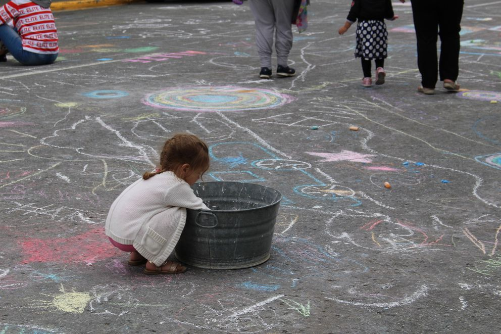 A girl looks through chalk in a bin during a chalk event at the Downtown Summer Solstice Festival Saturday. June 22, 2019 (Photo by Lauren Ellenbecker)