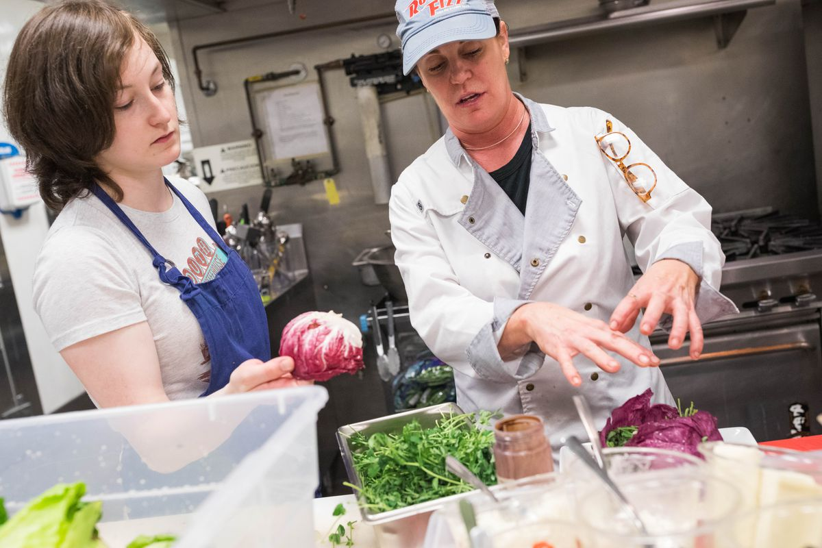Chef Laura Cole instructs Alex Debon at Muse on Tuesday, July 16, 2019. (Loren Holmes / ADN)