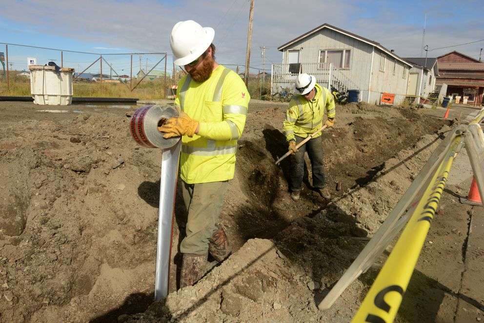 Zachary McGee and Dalton Zmak lay warning tape above the fiber-optic cable being buried along a street in Nome on Aug. 22, 2016. (Bob Hallinen / Alaska Dispatch News)