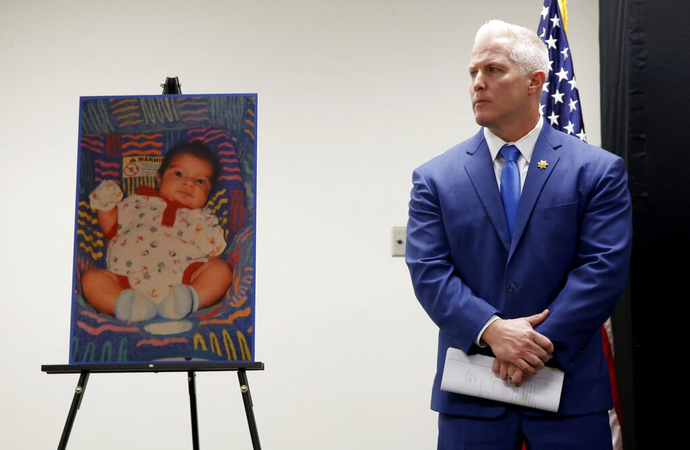 Yolo County District Attorney Jeff Reisig stands next to a photo of Kato Krow Perez, born in 2001, one of five infants believed to be killed by their father, during a news conference in Woodland, Calif., Monday, Jan. 27, 2020. Paul Perez, the father of the infants, has been arrested in the decades-old killings of five of his infant children, a case the sheriff said had haunted his agency for years, the Yolo County Sheriff's Office said Monday, Jan. 27, 2020. (AP Photo/Rich Pedroncelli)