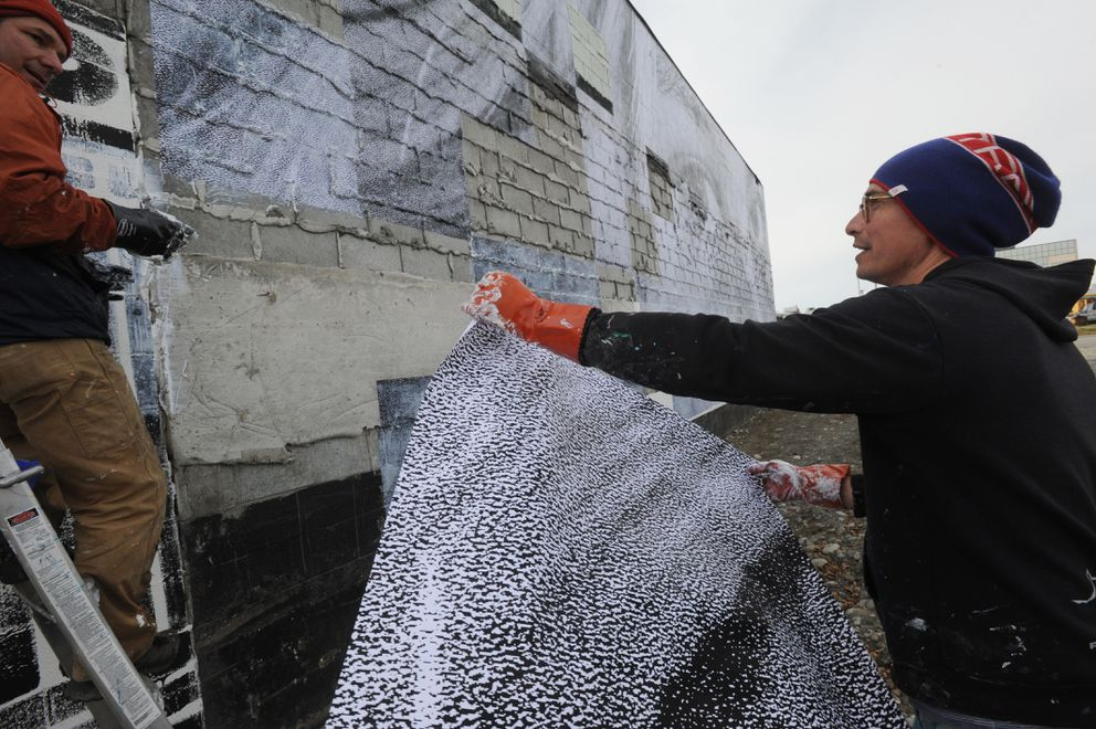 Photographer Michael Conti, left, and artist James Temte collaborated on a wheat paste mural installation on a building next to the vacant lot where the Paradise Inn once stood in Spenard on Sunday, Sept. 22, 2019. (Bill Roth / ADN)