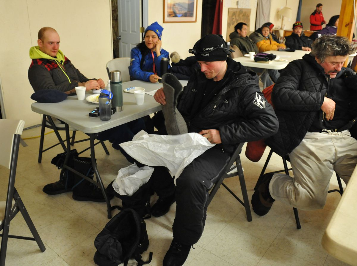 Iditarod mushers Wade Marrs and Dallas Seavey sit across from each other as Seavey assembles his footgear in the Unalakleet checkpoint Sunday. (Bob Hallinen / Alaska Dispatch News)