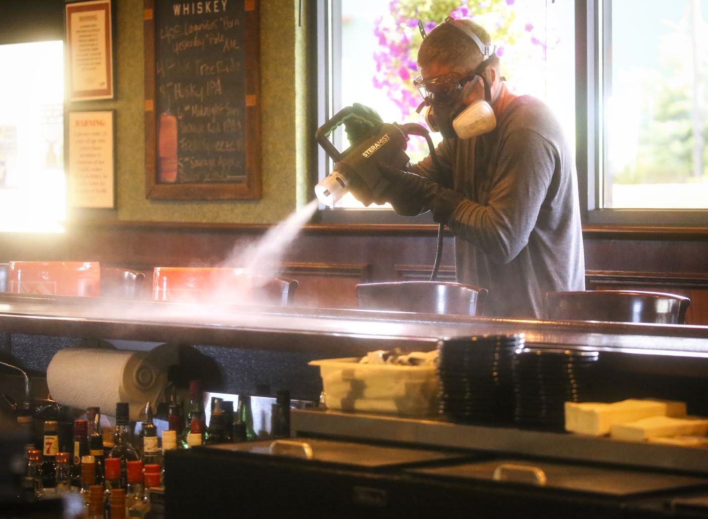 JULY 20. Brent Aafedt with Alaska Disinfectant Services uses SteraMist ionized Hydrogen Peroxide technology to thoroughly disinfect the interior of 907 Alehouse & Grill. The extra cleaning measures were taken after an employee at the alehouse tested positive for COVID-19. (Emily Mesner / ADN)