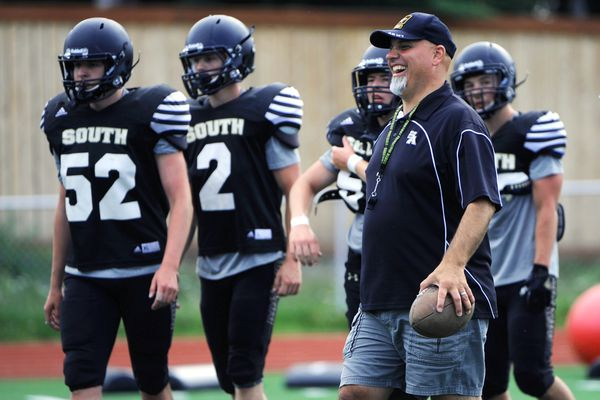 Head coach John Lewis is encouraging an upbeat attitude following last year's losing season during football practice on Tuesday, August 8, 2017, at South. (Erik Hill / Alaska Dispatch News)