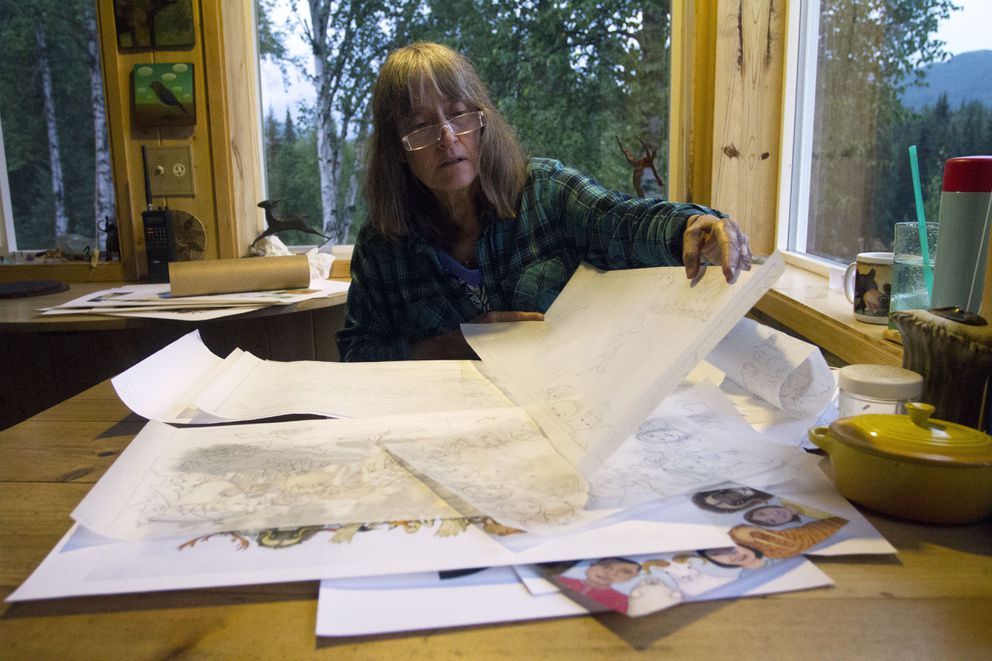 """Shannon Cartwright spreads out her artwork on the kitchen table for her upcoming children's book called """"Alaska Animals, You and I."""" It took Cartwright almost three years to illustrate and write the story. (Sarah Bell / Alaska Dispatch News)"""