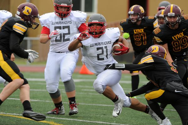Reginald Drummond, of Wasilla, gains some ground as Jaili Rescober, of Dimond, gets a hand on him at the Dimond High in Anchorage, AK on Saturday, Aug 11, 2018. Dimond High defeated Wasilla High 35-21 in their opening football game of the season. (Bob Hallinen / ADN)