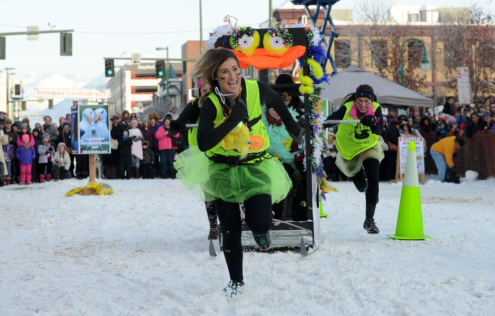 Lauren Maloney leads the Fabulous Flying Duck Farts team to the finish line during the Rondy Outhouse Races on Fourth Avenue in Anchorage on Feb. 25, 2017. (Bob Hallinen / ADN archive)