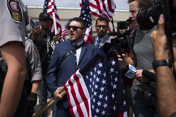 Jason Kessler, the organizer of the Unite the Right rally, is interviewed by reporters while police escort him into the Vienna metro station before they gather for a second Unite the Right Rally on the anniversary of last year's deadly Charlottesville demonstration on August 12, 2018 in Washington. MUST CREDIT: Washington Post photo by Calla Kessler