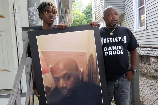 Joe Prude, brother of Daniel Prude, right, and his son Armin, stand with a picture of Daniel Prude in Rochester, N.Y., on Thursday, Sept. 3, 2020. Prude suffocated after police in Rochester put a