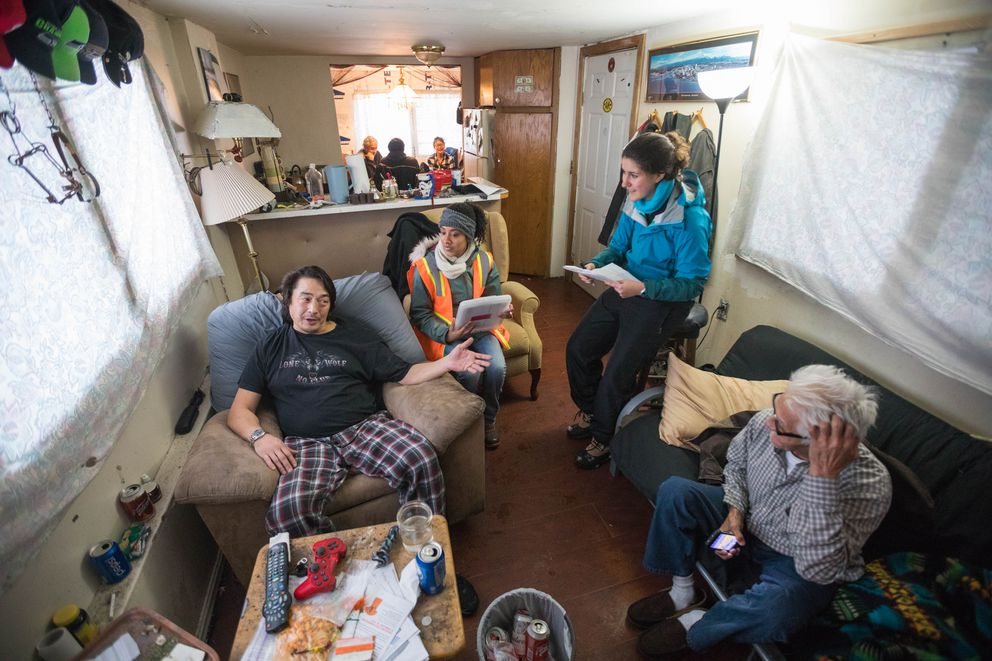 James Wilson, left, goes over fire safety plans with volunteers Guisselle Montes and Madison Ashley in his home at the South Park Estates mobile home park on Martin Luther King Jr. Day. Wilson had no working smoke alarms in his home, and the Red Cross installed three for free. (Loren Holmes / Alaska Dispatch News)