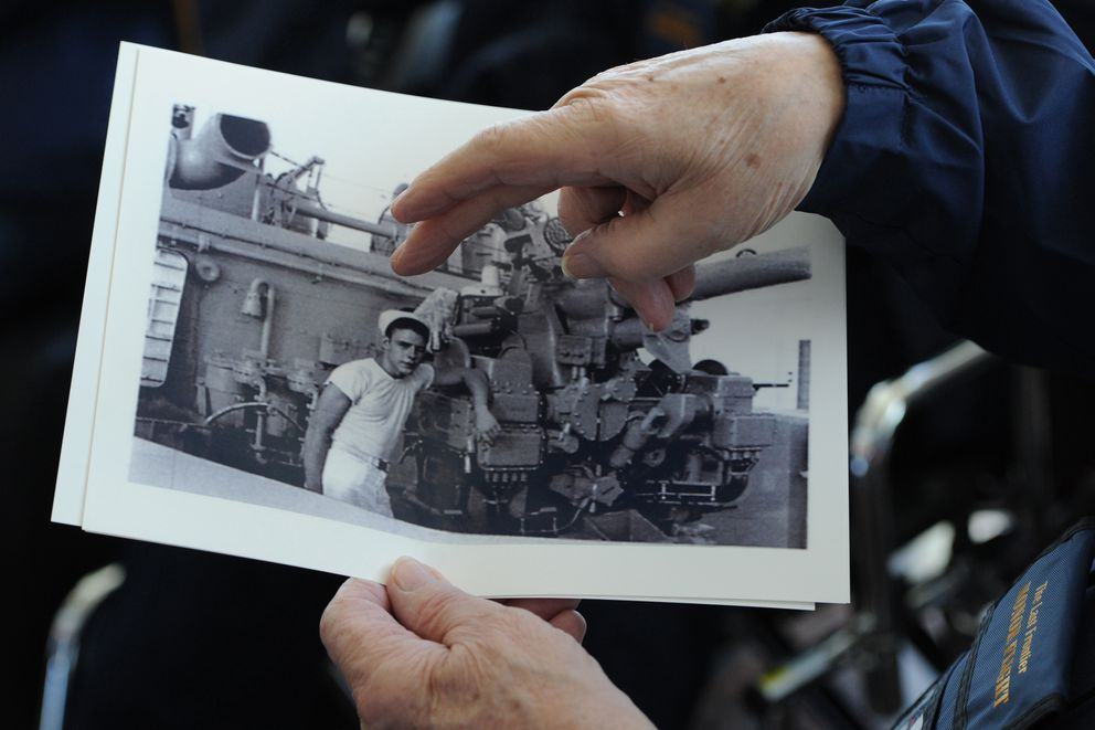 Korean War veteran Bob Roland, who served in the U.S. Navy, holds a photograph of himself standing next to a gun that was taken on his 21st birthday while in Guam. (Bill Roth / ADN)