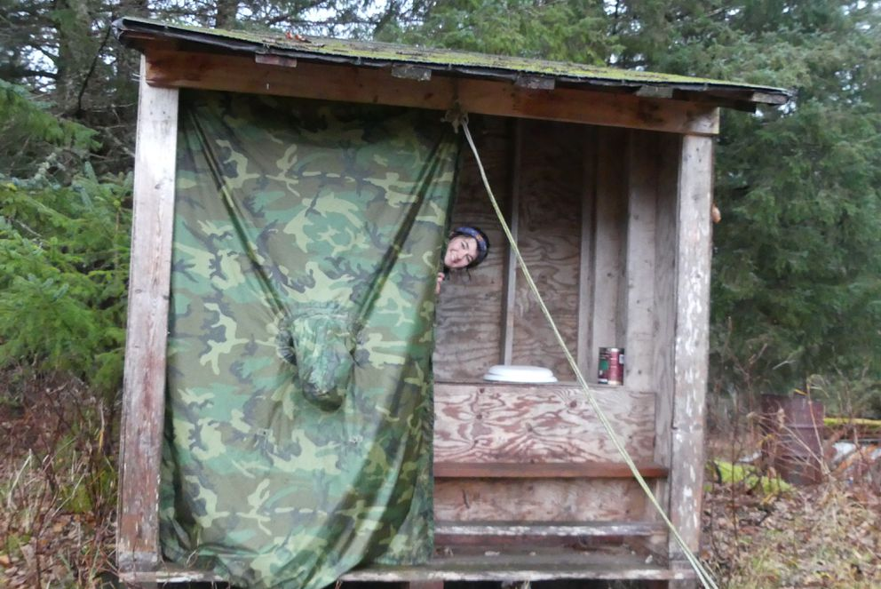 Megan Bush peeks around the temporary curtain/door of the outhouse at the Tenakee Springs cabin. (Rachel Friedlander)