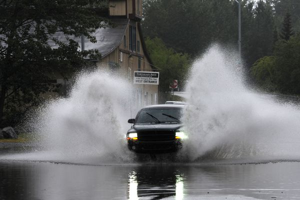 A motorist plows through a rain puddle at intersection of East Turnagain Boulevard and Borland Drive in Spenard on Sunday evening, July 24, 2016. (Bill Roth / Alaska Dispatch News)