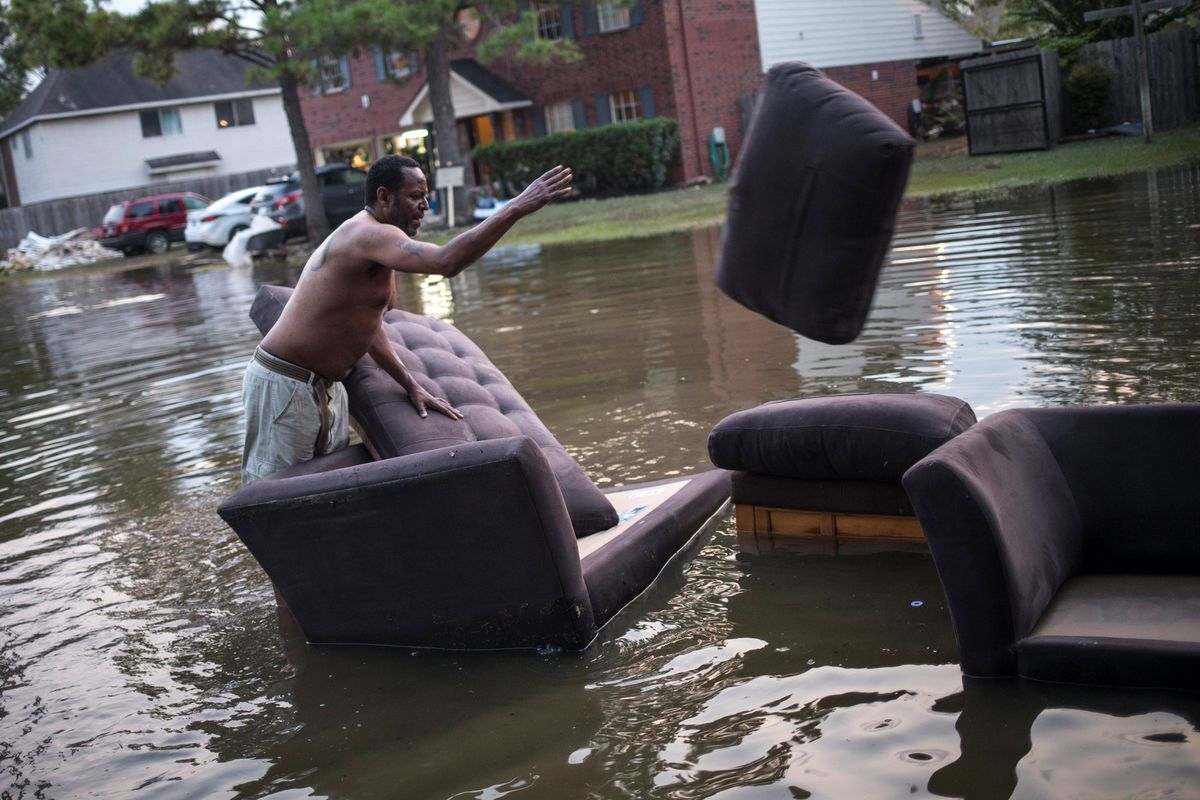 Vince Ware moves his sofas onto the sidewalk from his house, which was left flooded from Tropical Storm Harvey in Houston, Texas, on Sunday. (REUTERS / Adrees Latif)