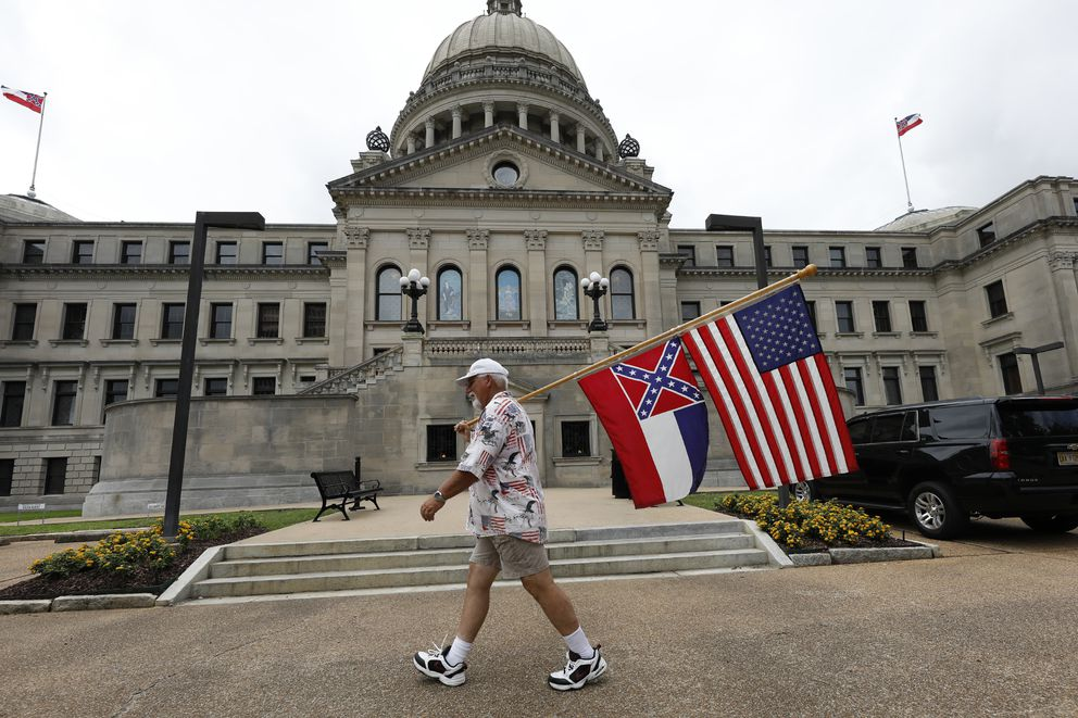 Dan Hartness of Ellisville, walks around the Capitol carrying the current Mississippi state flag and the American flag, Saturday, June 27, 2020, in Jackson, Miss. A supporter of the current flag, Hartness wanted to make his position known to lawmakers as he walked around the building for several hours. The current state flag has in the canton portion of the banner the design of the Civil War-era Confederate battle flag, that has been the center of a long-simmering debate about its removal or replacement. (AP Photo/Rogelio V. Solis)