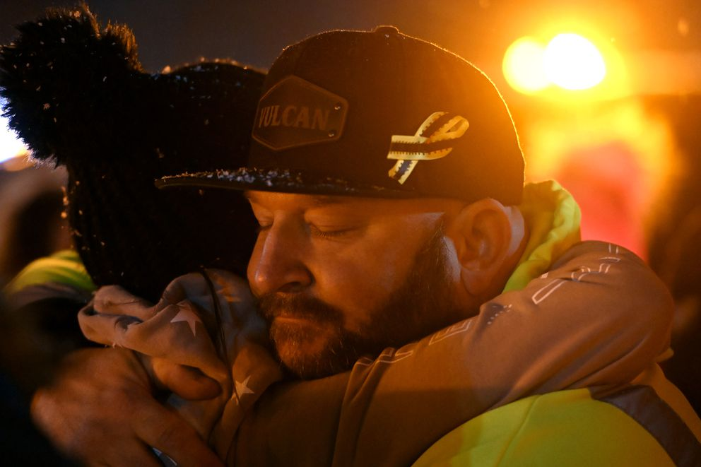 Vulcan Towing & Recovery owner Justin Creech gives an embrace during a celebration of life for fallen operator Hans Michael Moore on Wednesday evening. (Bill Roth / ADN)