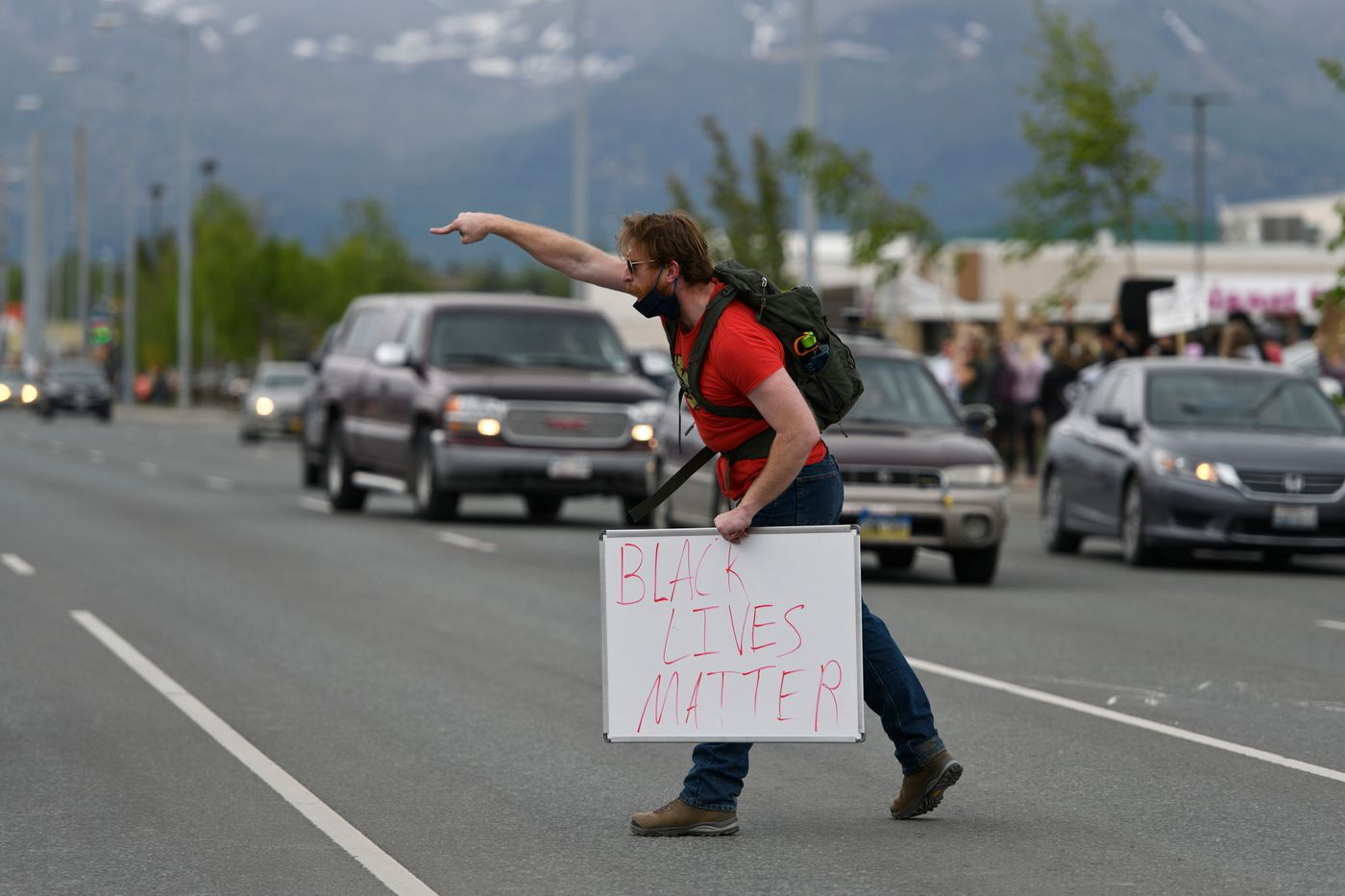 A protestor leads a chant on Northern Lights Bolevard. (Marc Lester / Anchorage Daily News)