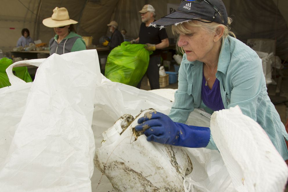 Judy Kowali digs through a bag to sort reusable items found in the Pacific Ocean during the Great Alaska Marine Debris Sorting Project at the Port of Anchorage on Saturday, July 16, 2016. The project started on Saturday and will end when the debris is all sorted or after 10 days, whichever comes first. Chris Pallister, head of GoAK, is expecting to finish in 5 days based on the number of volunteers that helped on Saturday. (Sarah Bell / Alaska Dispatch News)