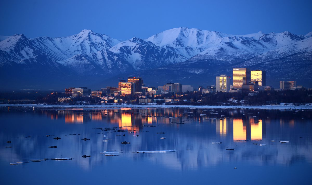 The buildings of downtown Anchorage reflect the color in the sky just after sunset back-dropped by the Chugach Mountains and reflected in the calm waters of Knik Arm on Tuesday, April 11, 2017. (Bob Hallinen / Alaska Dispatch News)