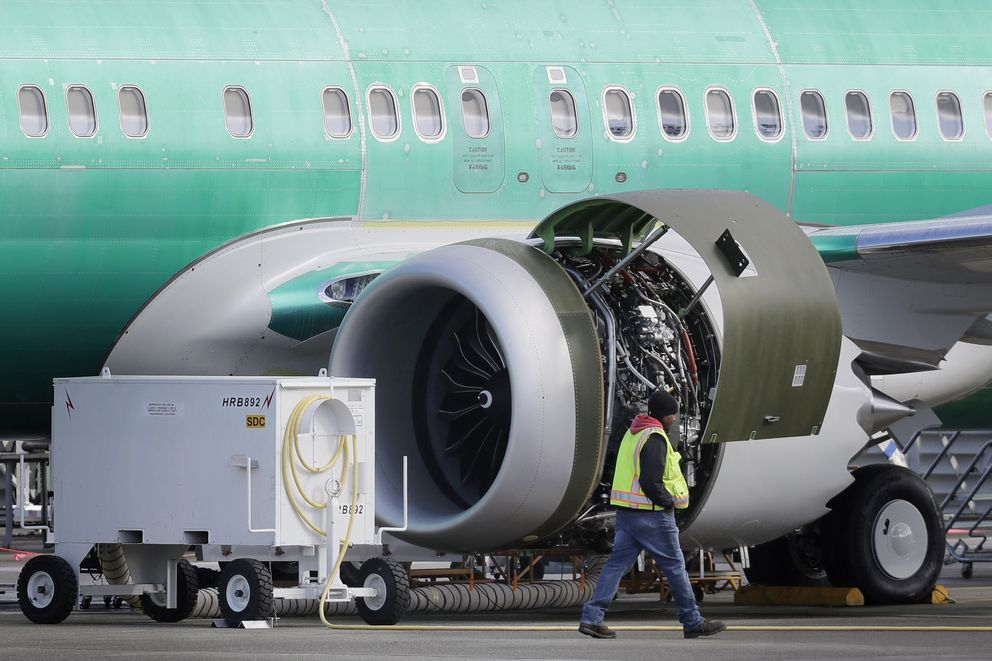FILE- In this March 13, 2019, file photo a worker walks past an engine on a Boeing 737 MAX 8 airplane being built for American Airlines at Boeing Co.'s Renton assembly plant in Renton, Wash. U.S. prosecutors are looking into the development of Boeing's 737 Max jets, a person briefed on the matter revealed Monday, the same day French aviation investigators concluded there were