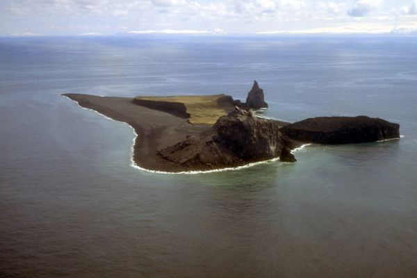 Aerial photo taken May 10, 1994, looking south at Bogoslof Island, which is the summit of a largely submarine stratovolcano located in the Bering Sea 31 miles behind the main Aleutian volcanic arc. The island, due to energetic wave action and frequent eruptive activity, has changed shape dramatically since first mapped in the late 1700s. (Photo by T. Keith / U.S. Geological Survey via Alaska Volcano Observatory)