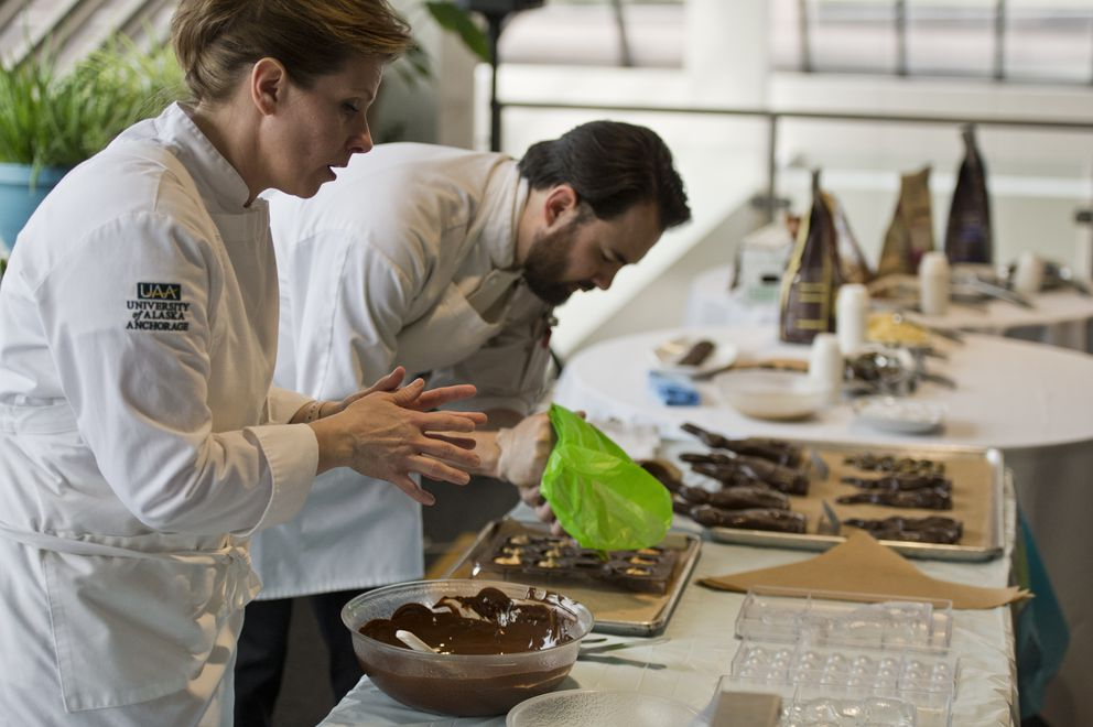 Kellie Puff, left, hosted a chocolate workshop at the UAA Campus Bookstore on April 4, 2019. Student Kyle Furuuchi assists at right. (Marc Lester / ADN)