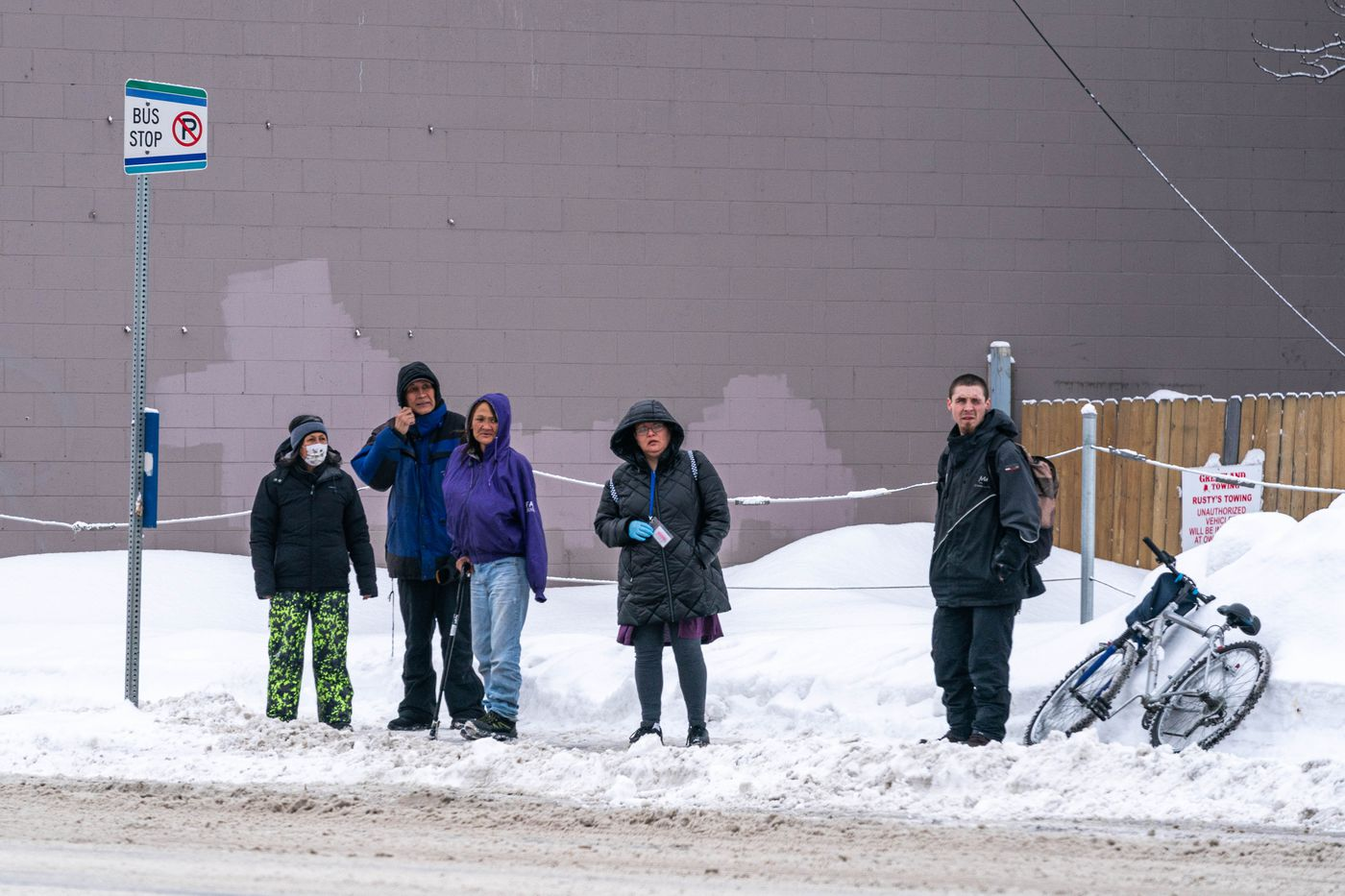 People wait for a public bus on 4th Avenue in downtown Anchorage on Wednesday, March 18, 2020. (Loren Holmes / ADN)