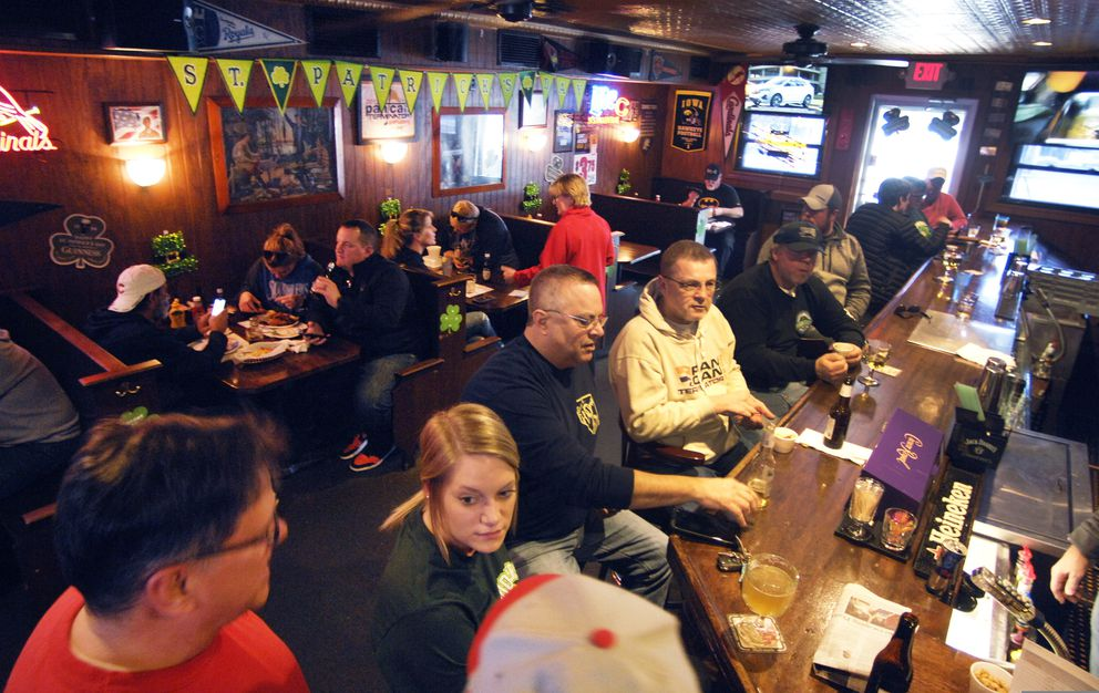 Customers eat and drink at Schooners, in Bloomington, Sunday, March 3, 2020, after Illinois Gov. JB Pritzker announced that dine-in service would be halted in restaurants and bars across Illinois. (David Proeber/The Pantagraph via AP)