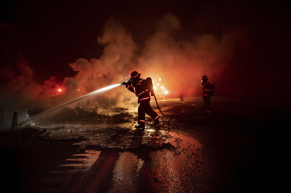 A firefighter sprays the smoldering remains of a vehicle on Interstate 5 as the Delta Fire burns in the Shasta-Trinity National Forest, Calif., on Wednesday, Sept. 5, 2018. Parked trucks lined more than two miles of the highway as both directions remained closed to traffic. (AP Photo/Noah Berger)